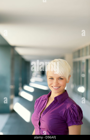 portrait of confident attractive business woman smiling and looking at camera out of office building. Copy space - Stock Image
