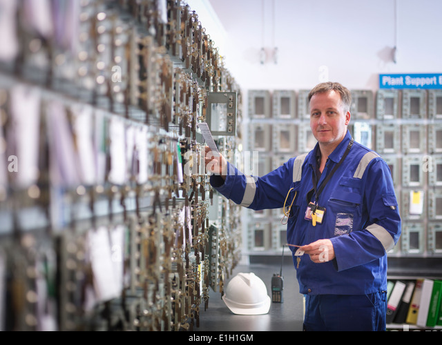 Portrait of engineer selecting equipment keys in power station - Stock Image