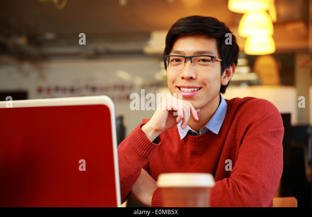 Cheerful asian man sitting at the table with laptop and looking at camera - Stock Image