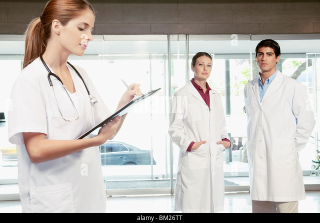 Female nurse writing on a clipboard with her colleagues standing in the background - Stock Image