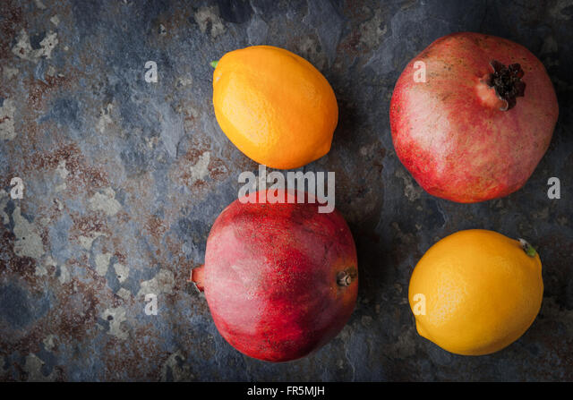 Lemons, pomegranates on the stone table horizontal - Stock Image