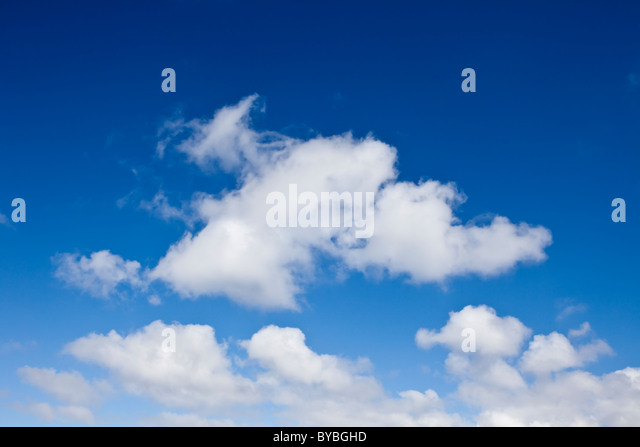 Fluffy cumulus clouds and a blue sky - Stock Image