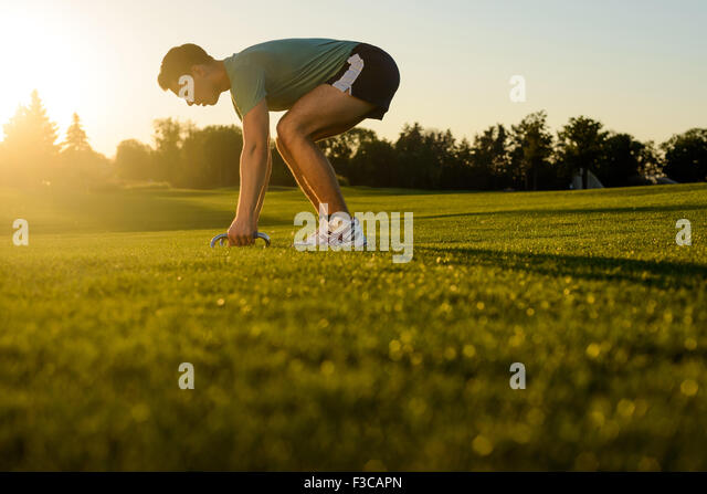 Guy shakes his muscles on the nature. - Stock Image