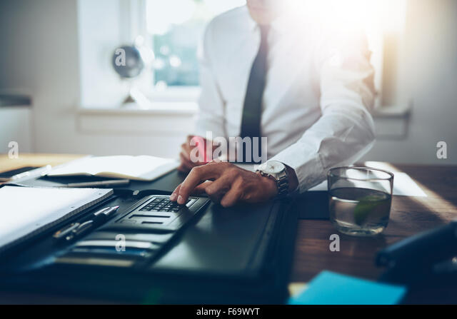 close up, business man or lawyer accountant working on accounts using a calculator and writing on documents - Stock-Bilder