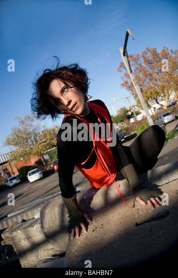 Athletic woman in cat like pose in car park for fashion shoot - Stock Image