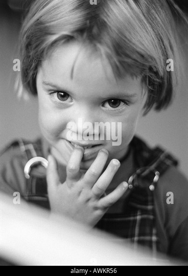 Little girl with finger in mouth, portrait, b&w - Stock Image