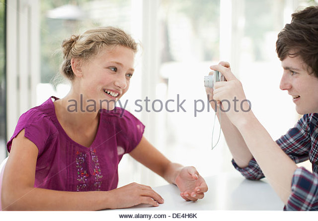 Brothers and sister taking photograph with digital camera - Stock Image