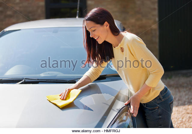 Woman washing and wiping car with cloth in sunny summer driveway - Stock-Bilder