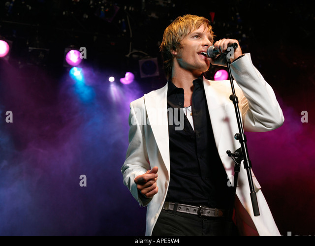 Young Man Singing into microphone on stage at Concert, low angle view - Stock Image