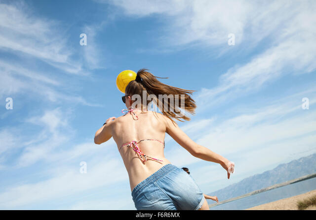 Young woman playing beach volleyball - Stock Image