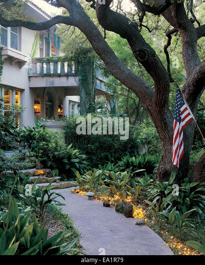 lit garden path with American flag leads to front door of stone house - Stock-Bilder