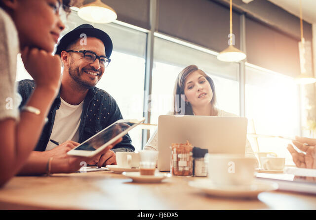 Portrait of happy young man sitting and talking with friends at a cafe. Young people at a coffee shop with digital - Stock-Bilder