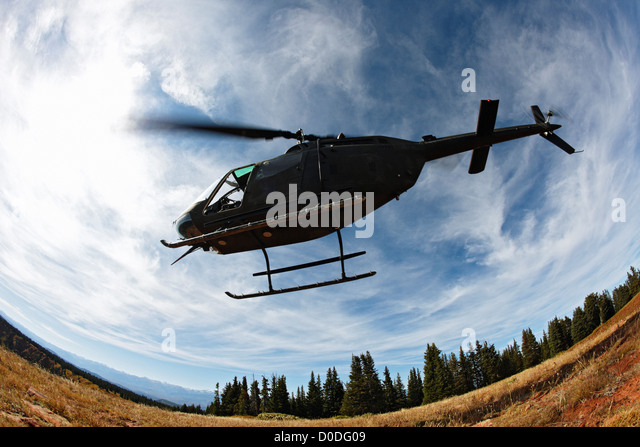An OH-58 Kiowa Colorado Army National Guard lifts off edge cliff 11,000 feet in Colorado's Rocky Mountains. - Stock Image