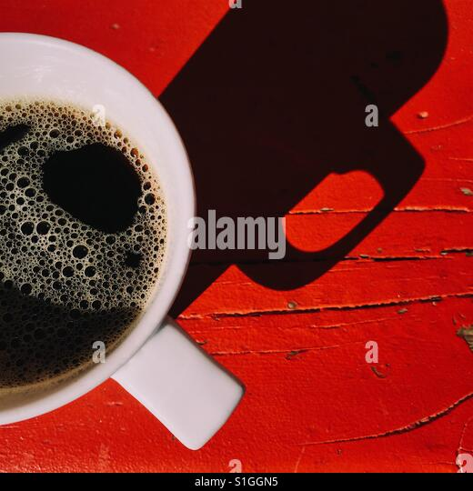 An overhead close-up shot of a fresh cup of black coffee on a red wooden table. A simple composition with a dark - Stock-Bilder