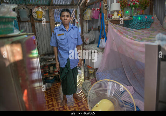 A poor Thai man poses at home in Phuket, Thailand. Nine is a security guard for a luxury property. 09-Mar-2017 - Stock Image