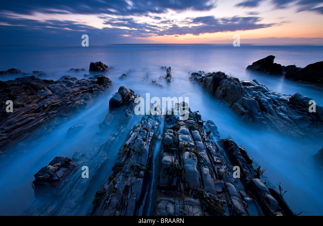 Advancing tide on the rocky ledges of Sandymouth, Cornwall, England - Stock Image