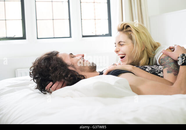 A cool young couple lying on a bed laughing together. - Stock Image
