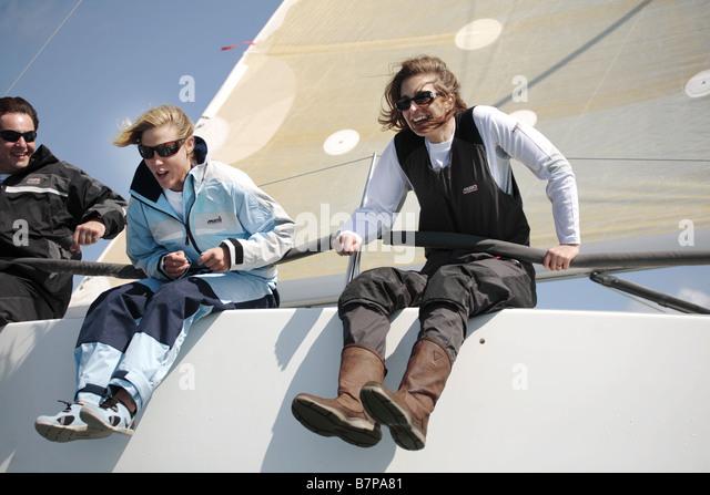 3 sailors, 2 female 1 male having fun on a yacht. - Stock Image