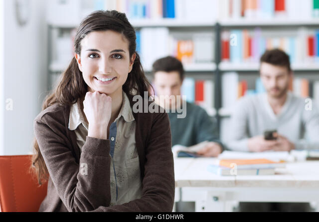 Smiling young student at the library looking at camera, her schoolmates are sitting at desk on background - Stock Image