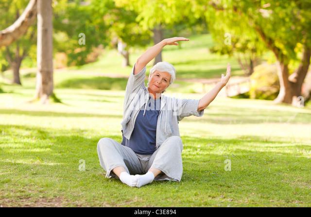 Senior woman doing her stretches in the park - Stock-Bilder