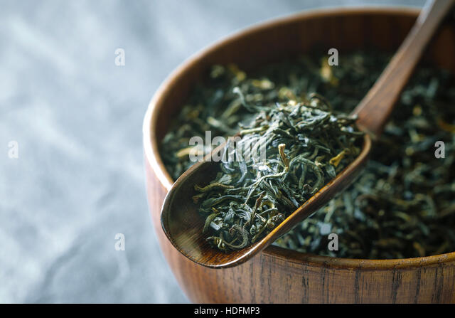 Tea leaves on the wooden bowl on the  dark stone background horizontal - Stock Image