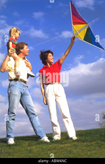 Young couple in their 20s have fun together flying a kite with their young daughter - Stock Image