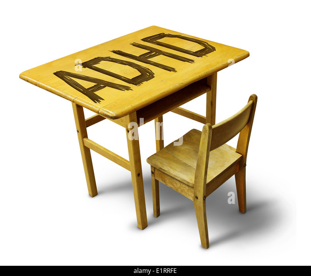 ADHD Concept for hyperactivity disorder and attention deficit behavior as a school desk with the letters carved - Stock Image