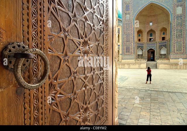 The Mir-i-arab Madrassah seen beyond the ornate carved doors of the Kalon Mosque, Bukhara, Uzbekistan - Stock-Bilder