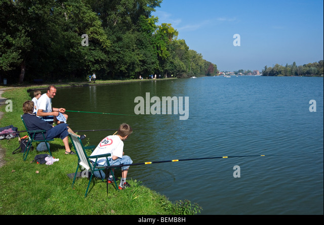 Family, father and sons with fishing rods angling in lake Donkmeer, East Flanders, Belgium - Stock Image