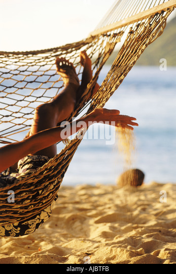 Woman in hammock with beach sand dripping through fingers - Stock Image