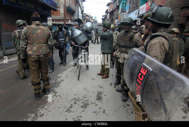 A kashmiri muslim crosses road  as indian police petroling before a protest in Srinagar,the summer capital of indian - Stock Image