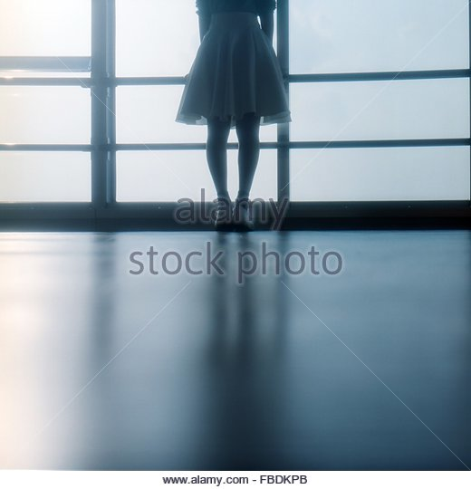 Rear View Low Section Of Woman Standing Against Window - Stock Image