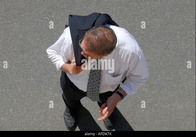 Man carrying jacket over shoulder, France. - Stock Image