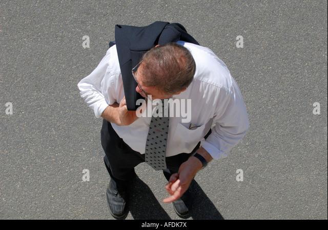 Man carrying jacket over shoulder, France. - Stock Image