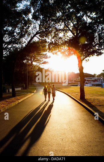 Mother and children walking on path in sunlight - Stock Image