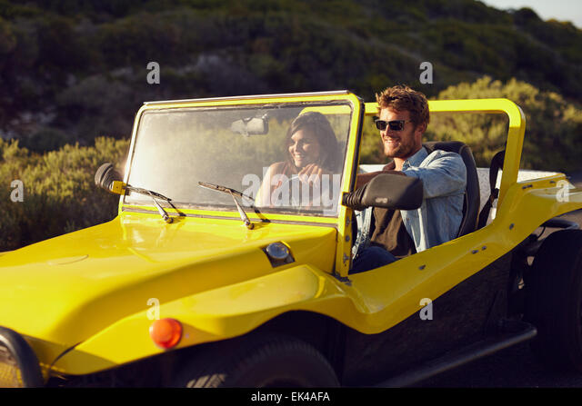 Shot of a handsome young man driving a buggy car in the countryside with his girlfriend. Cheerful young couple on - Stock Image