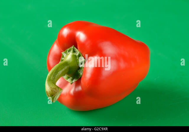 Red bell pepper on green chopping board - the correct colour board for food hygiene requirements - Stock Image