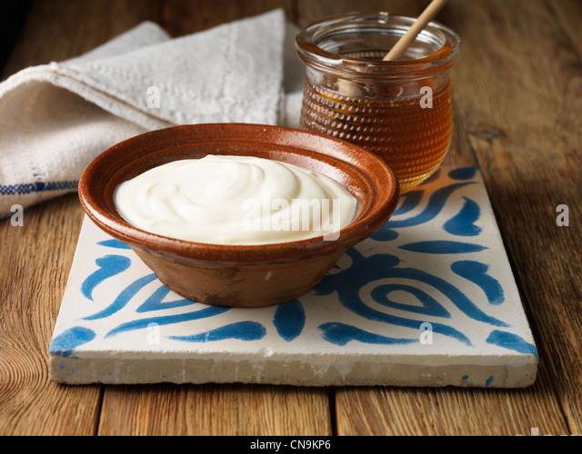 Greek yogurt and honey on tile - Stock Image