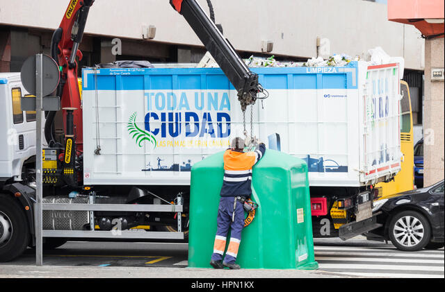 Recycling Spain. Council worker emptying container full of glass bottles in city street in Spain. - Stock Image