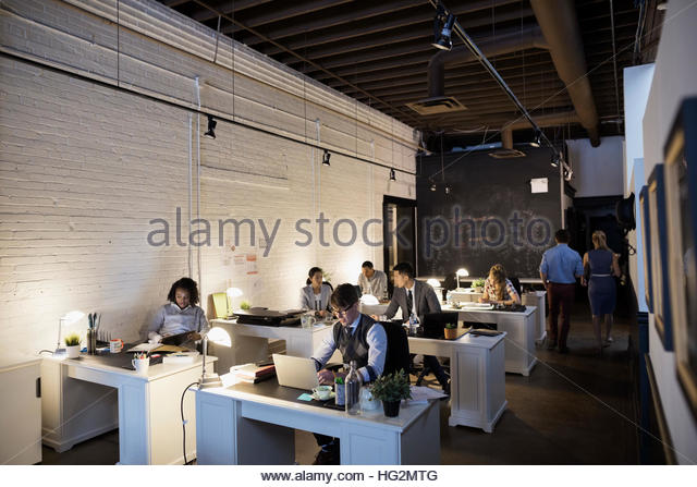 Creative business people working in open plan office - Stock Image