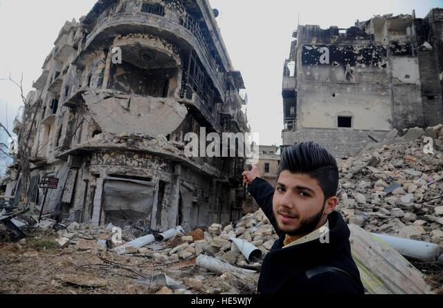 Aleppo, Syria. 17th Dec, 2016. A man points to a building where he used to live in at the old city of Aleppo, Syria, - Stock-Bilder