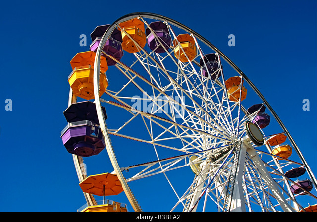 Pacific Park, Santa Monica CA pier family amusement park large Ferris wheel Roller Coaster moving over the ocean - Stock Image