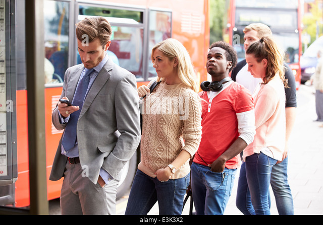 Queue Of People Waiting At Bus Stop - Stock Image