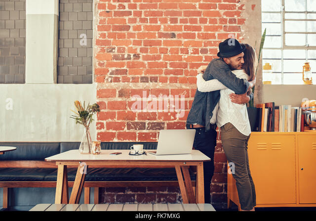 Portrait of man and woman hugging and greeting each other at a coffee shop, couple meeting in a cafe. - Stock-Bilder