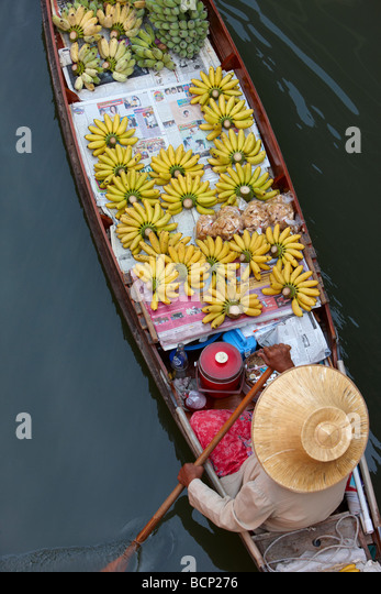a woman paddling a boat selling bananas at the floating market at Damnoen Saduak, nr Bangkok, Thailand - Stock Image