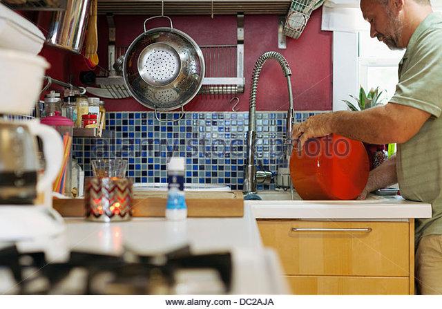 Man washing red pot - Stock-Bilder