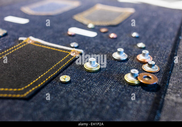 Buttons on denim fabric in factory - Stock Image