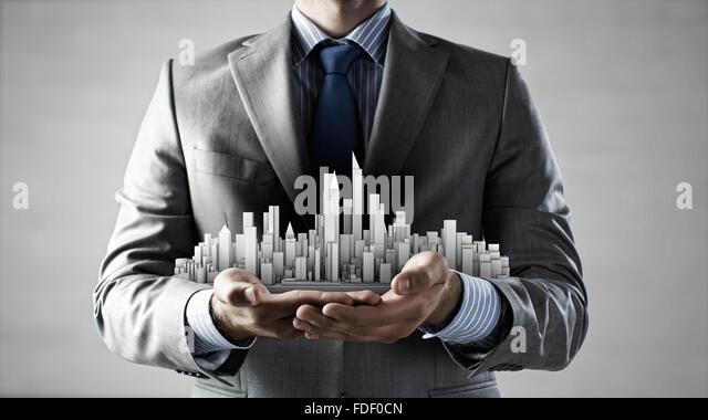 Close up of businessman hand holding construction model - Stock-Bilder