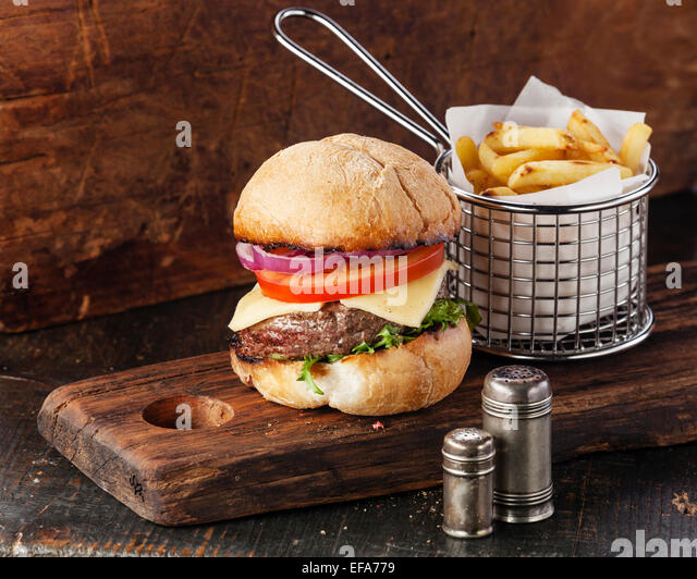 Burger with meat and French fries in basket on wooden background - Stock-Bilder
