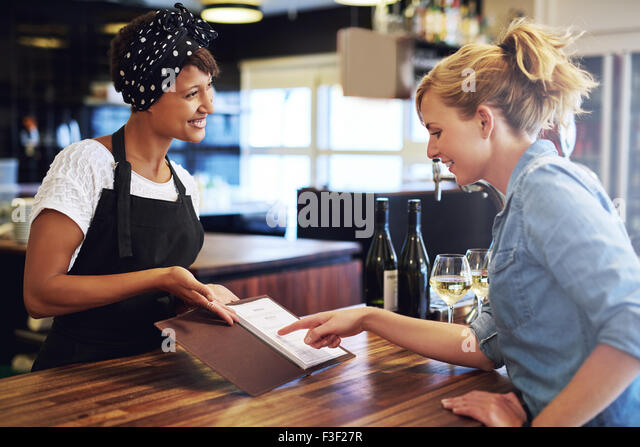 Female customer choosing wine from a wine list being presented to her by a charming young African American bartender - Stock Image